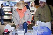 28 NOVEMBER 2006 - SAN LUIS, AZ: Farm workers get breakfast from taco vendors after entering the US at the Port of Entry in San Luis, AZ, about 20 miles south of Yuma. Farmers and agricultural producers around Yuma, AZ, are facing a growing shortage of farm workers. Increased border enforcement have deterred many illegal workers from seeking work in Arizona and long lines at the ports of entry for legal workers are leading to the labor shortage. Some labor contractors are reporting as much as a 40 percent shortage of farm workers, Yuma farmers planted 15 percent fewer acres this year, compared to last, because of the shortage. More than 100,000 acres of iceberg lettuce are cultivated in Yuma county and more than 50,000 people are employed as seasonal farm workers at the height of the harvest, which is December through February. Nearly 3,500 seasonal farm workers stand in line for up to two hours every morning at the San Luis, AZ, Port of Entry to enter the US legally to work in the fields. Experienced workers can make as much as $14 (US) per hour during the harvest.  Photo by Jack Kurtz