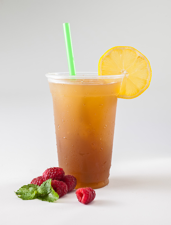 Red rapberry leaf tea slushy with lemon garnish and raspberry and mint in a to-go cup with a green straw.