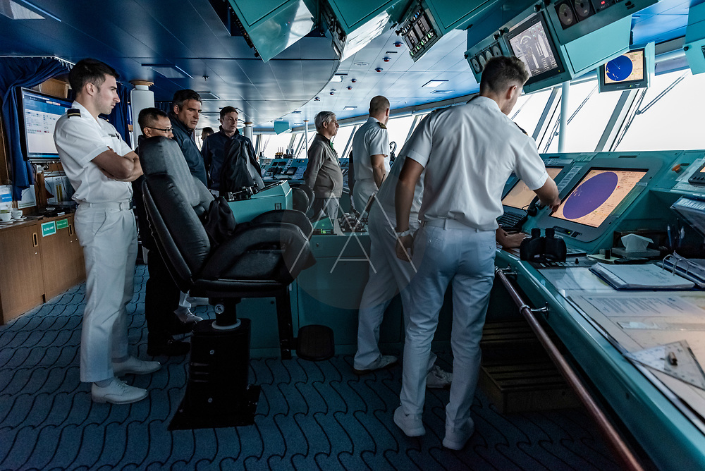 Cape Horn, Argentina - 02 February 2019: View of the captain with his crew leading a difficult manoeuvre sailing near Cape Horn and the Drake channel, Argentina.