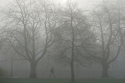 © Licensed to London News Pictures. 01/04/2014. Hammersmith, UK. A commuter walks across the park.  A foggy morning in Ravenscourt Park in Hammersmith West London today April 1st 2014. Photo credit : Stephen Simpson/LNP