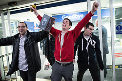 © Licensed to London News Pictures . 27/11/2015 . Salford , UK . People cheer as they leave a branch of Tesco in Pendleton , Salford , with a pair of headphones this morning (Friday 27th November) as people behind queue for Black Friday offers . Last year (2014) scuffles and fights were reported amongst queuing bargain-hunters . Photo credit: Joel Goodman/LNP