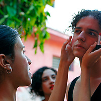 Central America, Cuba, Santa Clara. Dancers and performers apply make-up to one another's faces at the Santa Clara Musical School of Art, Cuba.