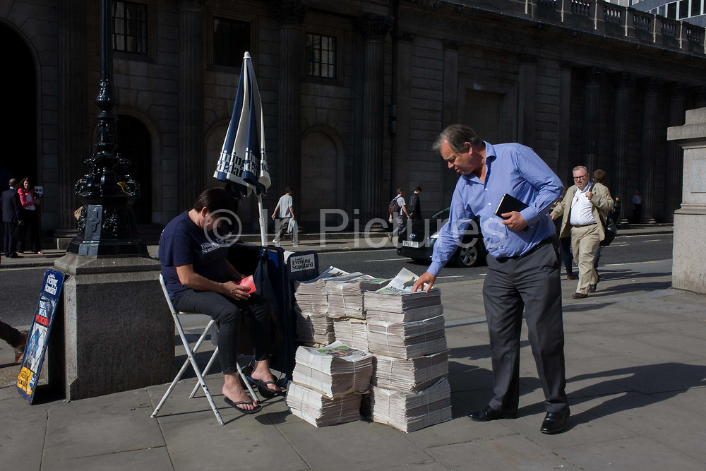 Evening Standard newspaper stand at Cornhill in the City of London.  A businessman pauses to pickup up his copy of the free London paper before continuing his journey home, from this area in the heart of the capital's financial heart, known as the Square Mile. The Standard's vendor minds the piles of newsprint stacked on the pavement. The Evening Standard is owned by Russian-born proprietor, Evgeny Alexandrovich Lebedev.