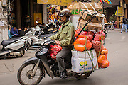 01 APRIL 2012 - HANOI, VIETNAM: A man on a motorcycle makes business deliveries in the Old Quarter of Hanoi, the capital of Vietnam. Hanoi recently celebrated its 1000th Anniversary, making it one of the oldest permanently inhabited cities in Asia.    PHOTO BY JACK KURTZ