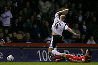 Jay McEveley (standing) of Derby is tackled by Colchester skipper Karl Duguid (grounded)