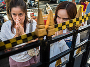 19 AUGUST 2015 - BANGKOK, THAILAND: Thais pray outside Erawan Shrine while Buddhist monks conduct a service for people who died in the bombing at the shrine. Erawan Shrine in Bangkok reopened Wednesday morning after more than 20 people were killed and more than 100 injured in a bombing at the shrine Monday, August 17, 2015. The shrine is a popular tourist attraction in the center of Bangkok's high end shopping district and is an important religious site for Thais. No one has claimed responsibility for the bombing.       PHOTO BY JACK KURTZ