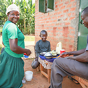 CAPTION: Catherine is all smiles as she serves food to her first-born child Innocent and her husband David. In Uganda, it is traditional for women to kneel down when serving their menfolk. LOCATION: Apapai Parish, Otuboi Sub-county, Kalaki County, Kaberamaido District, Uganda. INDIVIDUAL(S) PHOTOGRAPHED: From left to right: Catherine Anaso, Innocent Jacob Okot and David Alele.