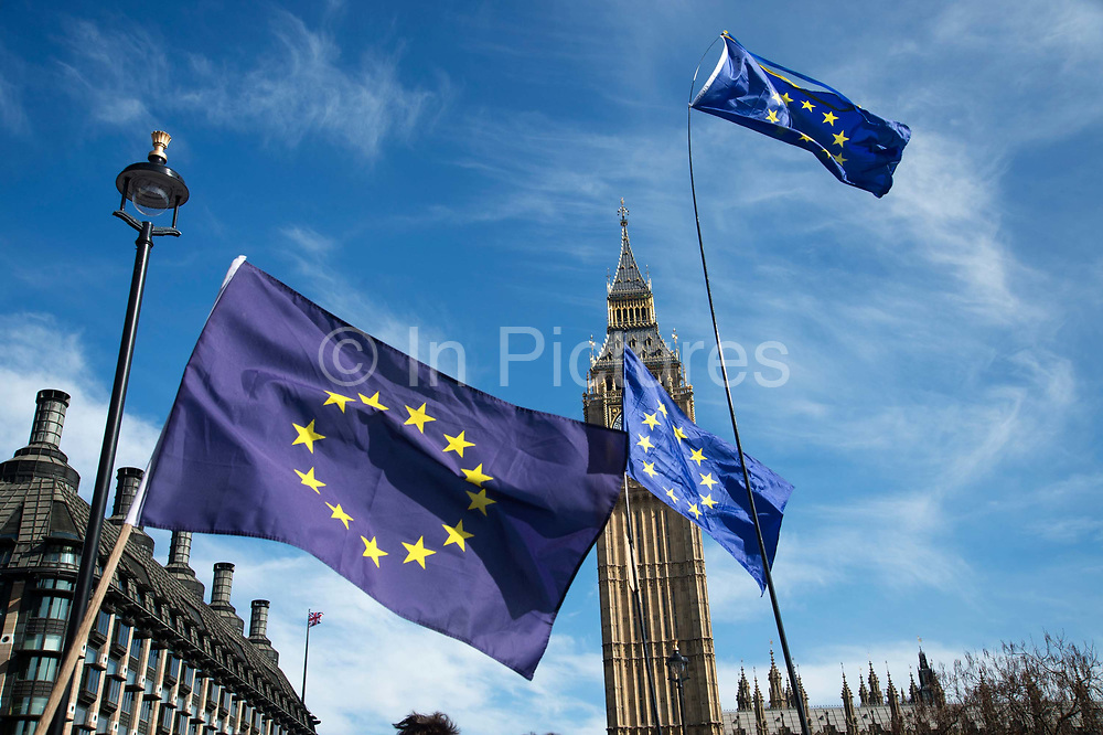 Hundreds of thousands of people protest in the Unite for Europe March on Parliament against Brexit demonstration on 25th March 2017 in London, United Kingdom. The march in the capital brings together protesters from all over the country, angry at the fact that Article 50 will be invoked and to listen to the 48 percent of British voters who voiced against Brexit. Since the vote was announced, there have been demonstrations, protests and endless political comment in all forms of media. Half of the country very displeased with the result and the prospect of being taken out of the European Union against their will, and with uncertainty as to what will happen next in the politics surrounding the exit from Europe. EU flags , blue with yellow stars , flutter in front of Big Ben.