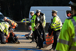 Ockham, UK. 21st September, 2021. Surrey Police officers carry an Insulate Britain climate activist from the clockwise carriageway of the M25 between Junctions 9 and 10. Activists briefly halted traffic on both carriageways of the motorway as part of a campaign intended to push the UK government to make significant legislative change to start lowering emissions.