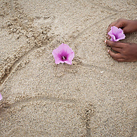Vijitha places flowers in the sand on the beach close to the location of her mother's death in the tsunami. <br />