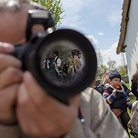 Folk dancers are reflected on the lens of a photographer during an easter celebration in the Skanzen open air folk museum in Szentendre, Hungary on April 08, 2012. ATTILA VOLGYI