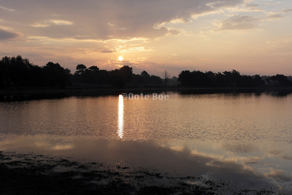 a beautiful idealistic sunrise landscape with water and cloud reflection Holland