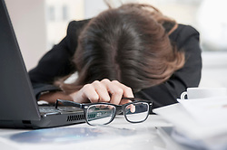 Young over-burdened businesswoman with head on desk at her workplace