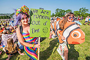Reaching the Sacred stones a giant human version of their hour glass logo is created - The Extinction Rebellion protest march around the site, led by their Iconic pink boat, Tell the Truth - The 2019 Glastonbury Festival, Worthy Farm. Glastonbury, 27 June 2019