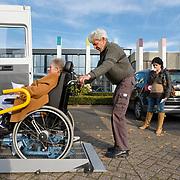 Foto: David Rozing  Etten Leur Ouderen. Oudere vrouw in rolstoel wordt geholpen, zij wordt via een laadklep in de autobus geplaatst, uit bus gehaald. Vervoer op maat, afhankelijkzijn, zorgkosten. , broze gezondheid, broos, broze,,  regiotaxi, retired, retirement, rollator, rolstoel, samen, samen leven, samen werkt beter, samenleven, samenleving, samenwerken, samenwerking, senioren, seniors, slecht ter been, sociale banden, sociale cohesie, sociale samenhang, speciaal vervoer, sterftecijfer, steun, steunen, steunen op, stokoud, stokoude, straatbeeld, taxi, taxibus, te been blijven, te voet, tezamen, together, transporteren, transportmiddel, transportmiddelen, uit de auto helpen, uitrusten, uitstappen uit auto, uitzicht, van a naar b gaan, vergankelijk, vergankelijke, vergankelijkheid, vergrijzen, vergrijzende samenleving, vergrijzing, vervoer op maat, vervoer ouderen, vervoermiddel, vervoersmiddel, vijftig plusser, vitaal, vitale, vitaliteit, voetganger, voetganger  voetgangers, voorjaar, vrijwilliger, vrijwilligerswerk, vrouw, vrouwen, wagentje, wandelstok, wankel, wankele tred, zelfstandig leven, zelfstandig zijn blijven, zelfstandigheid, zestig plus, zestig plusser, zestig plussers, zeventig plus, ziektekosten, zorgaanbieder, zorgaanbieders, zorgen voor, zorgkosten, zorgstelsel, zorgtaxi, zorgverzekeraars, zorgverzekering Foto: David Rozing