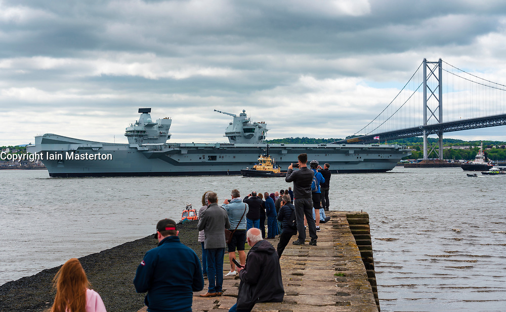North Queensferry, Scotland, UK. 23 May 2019. Aircraft carrier HMS Queen Elizabeth sails from Rosyth in the River Forth after a visit to her home port for a refit. She returns to sea for Westlant 19 deployment and designed to focus on the operations of her F-35 fighter aircraft. Pictured; People gathered at North Queensferry pier to watch the carrier depart the River Forth.