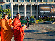 "20 JANUARY 2017 - BANGKOK, THAILAND: Buddhist monks wait to start the ""tak bat"" (alms giving ceremony) on the plaza in front of Bangkok's City Hall. Hundreds of municipal workers and civil servants made merit by praying and presenting alms to 89 Buddhist monks Friday to mark 100 days of mourning since the death of revered Bhumibol Adulyadej, the Late King of Thailand. The significance of 89 monks is that the King, who died on October 13, 2016, was a few weeks short of his 89th birthday.        PHOTO BY JACK KURTZ"