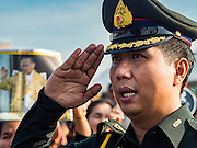 22 NOVEMBER 2016 - BANGKOK, THAILAND: A Thai military officer salutes while singing the national anthem at Sanam Luang Tuesday. Hundreds of thousands of Thais gathered across Thailand Tuesday to swear allegiance to the Chakri Dynasty, in a ceremony called Ruam Phalang Haeng Kwam Phakdi (the United Force of Allegiance). At Sanam Luang, the Royal Parade Ground, and location of most of the mourning ceremonies for the late King, people paused to honor His Majesty by singing the Thai national anthem and the royal anthem.       PHOTO BY JACK KURTZ