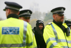 Hyde Park, London, 20/04/2014<br /> A woman stands behind a group of police officers at the pot-smoking day in Hyde Park, central London, organised by 420 Pro Cannabis group. Police were removing cannabis from people who were seen to be smoking joints. <br /> Photo: Anna Branthwaite/LNP