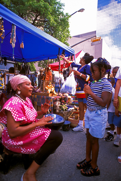 Stock photo of a woman playing a drum at her tent at the International Festival in downtown Houston Texas