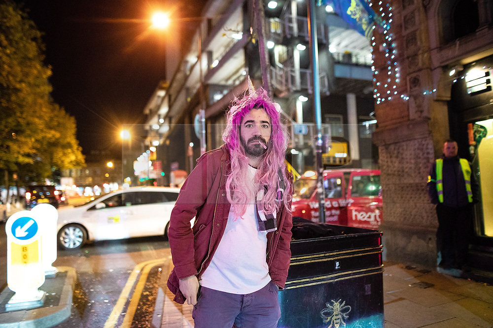 """© Licensed to London News Pictures . 28/10/2018. Manchester, UK. A man wearing a pink wig and unicorn horn , outside a club in Manchester's """" Gay Village """" . Revellers on a night out , many in fancy dress , on the weekend before Halloween . Photo credit: Joel Goodman/LNP"""