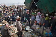 RUBBISH DUMP RECYCLING. South East Asia, Cambodia, Phnom Penh. Smokey Mountain, Steung Mean Chey, is Phnom Penh's municipal rubbish dump. Thousands work there, some 600 minors and 2000 adults, recycling the city's rubbish, dumped there by garbage trucks every day. The dump is notorious as many very young children work there. People eat and sleep overnight in the rubbish and fumes, under plastic tarpaulins or in the open air. They work 24 hours a day, like miners, with headlamps at night, collecting plastic, metals, wood, cloth & paper, which they sort and clean, weigh and sell, to be carried away for recycling. A day's work typically brings less than a dollar per person. One and a half to two dollars per day per family. The overpowering, acrid odour of grey smokey fumes blows across the dump, from which the place gets its name 'Smokey Mountain'. It can be smelt miles away. The shantytowns and squats, the recycling worker's homes butt onto or are inside the dump itself. There is no running water, sanitation and many are ill. Children often work with friends or relatives. Religious and ngo's help some children, but this is often resisted by families who need the extra income they generate.///Workers recycling fresh rubbish as it is dumped by the trucks. Workers have to collectively pay 50 cents $US, the driver abnd security, for this priviledge