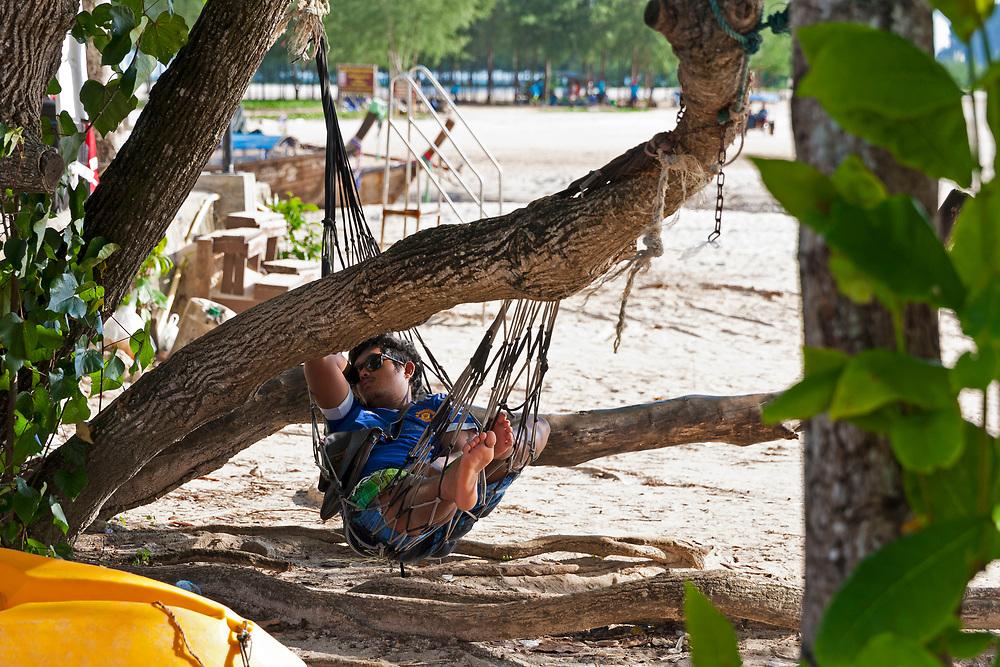 Local sleeping in hammock on beach, Krabi, Thailand.