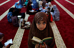 June 14, 2017 - Khan Younis, Gaza Stri - A Palestinian girl reads a copy of the Koran, Islam's holiest book, on the Muslim holy fasting month of Ramadan, at Hamad Mosque in Khan Younis in the southern Gaza Strip, June 14, 2017. Ramadan is sacred to Muslims because it is during that month that tradition says the Koran was revealed to the Prophet Mohammed. The fast is one of the five main religious obligations under Islam. More than 1.5 billion Muslims around the world will mark the month, during which believers abstain from eating, drinking, smoking and having sex from dawn until sunset  (Credit Image: © Ashraf Amra/APA Images via ZUMA Wire)