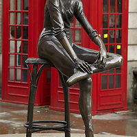 Young Dancer bronze statue by Enzo Plazzotta and  K2 telphone boxes in Broad Court, Covent Garden, London