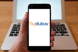 Using iPhone smartphone to display logo of Flydubai low-cost carrier from Dubai, UAE