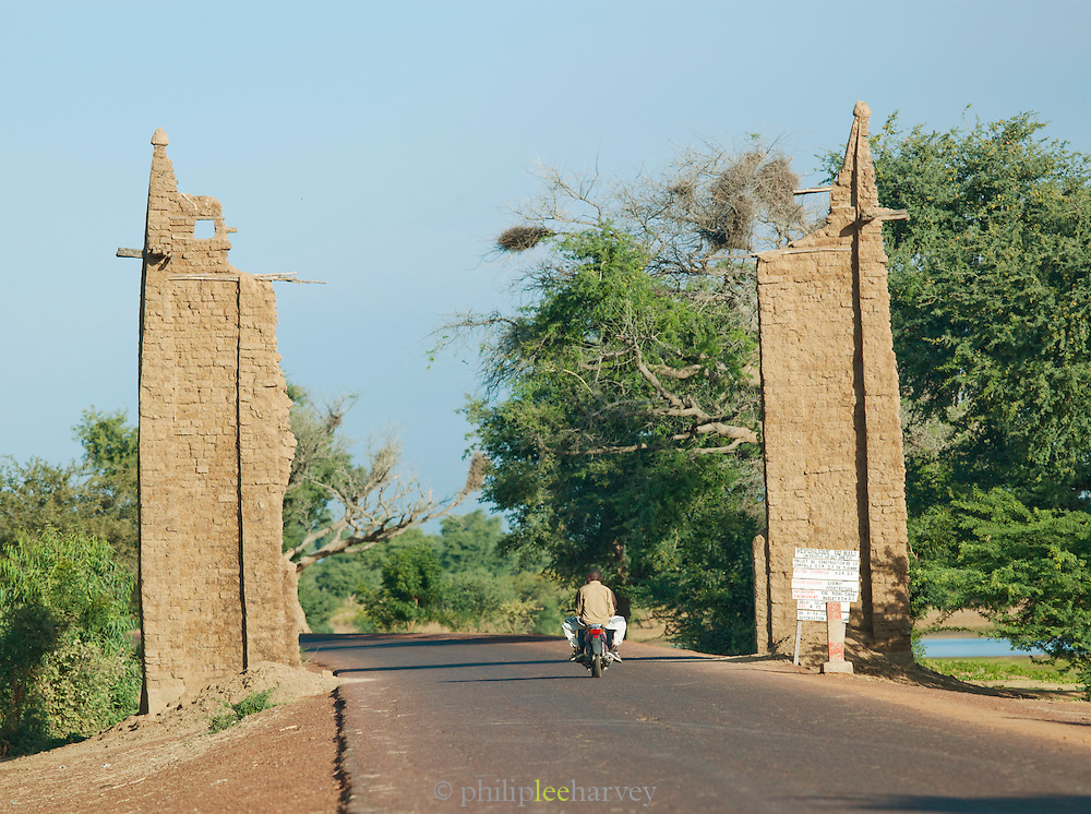 A motorcycle passes through the old city gate of Djenné, Mali