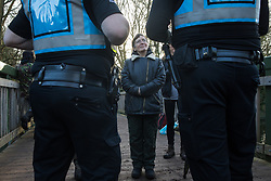 Denham, UK. 3 February, 2020. Police liaison officers speak to Sarah Green of Save Colne Valley as environmental activists occupy a bridge in Denham Country Park so as to seek to prevent works for the HS2 high-speed rail link including the felling of 200 trees and the construction of a Bailey bridge, compounds, fencing and a parking area. Part of the location for the work lies within a wetland nature reserve forming part of a Site of Metropolitan Importance for Nature Conservation (SMI). In spite of a substantial police presence, HS2 were not able to proceed with the work for the day.
