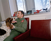 Pilot of the Red Arrows, Britain's RAF aerobatic team with his pet spaniel in the squadron crew room at RAF Scampton.