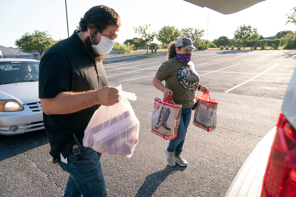 Staff members including Alejandro DelValle, l,  and Arlene Lozano help conduct a twice-weekly fresh food drive sponsored by Catholic Charities helping low-income Texans  make ends meet in Austin. The October 1, 2020 effort helped several hundred family members with fruit, meats, milk and cereal.