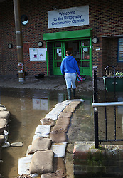© Licensed to London News Pictures. 24/02/2014. Basingstoke, Hampshire, UK. Kirsty Campbell (23) walking over a sandbag path into the Ridgeway Community Centre in Basingstoke to collect her food vouchers. Groundwater levels are continuing to rise in the area, forcing 69 homes to be evacuated in the Buckskin Area of the commuter town. The evacuees are currently being put up by the Council in local hotels. Photo credit : Rob Arnold/LNP