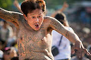 "23 MARCH 2013 - NAKHON CHAI SI, NAKHON PATHOM, THAILAND:  A man with a tiger tattoo rushes the stage at the Wat Bang Phra tattoo festival. Wat Bang Phra is the best known ""Sak Yant"" tattoo temple in Thailand. It's located in Nakhon Pathom province, about 40 miles from Bangkok. The tattoos are given with hollow stainless steel needles and are thought to possess magical powers of protection. The tattoos, which are given by Buddhist monks, are popular with soldiers, policeman and gangsters, people who generally live in harm's way. The tattoo must be activated to remain powerful and the annual Wai Khru Ceremony (tattoo festival) at the temple draws thousands of devotees who come to the temple to activate or renew the tattoos. People go into trance like states and then assume the personality of their tattoo, so people with tiger tattoos assume the personality of a tiger, people with monkey tattoos take on the personality of a monkey and so on. In recent years the tattoo festival has become popular with tourists who make the trip to Nakorn Pathom province to see a side of ""exotic"" Thailand. The 2013 tattoo festival was on March 23.    PHOTO BY JACK KURTZ"