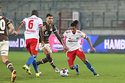 Fussball: 2. Bundesliga, FC St. Pauli - Hamburger SV, Hamburg, 01.03.2021<br /> Omar Marmoush (Pauli, m.) - David Kinsombi (l.) und Jeremy Dudziak (beide HSV)<br /> © Torsten Helmke