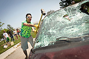 Victor Pinheiro '13 takes aim at the A-pillar of a junk car during the car smashing study break in the parking lot outside of the Harris Center. <br /> BEN BREWER/Grinnell College