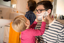 Son lathering his father for shaving, Munich, Germany