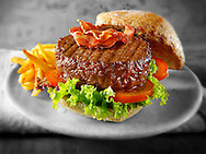 Beef burger with bacon in a wholemeal bun with salad and french fries