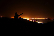 Israel, Eilat Mountains at night star gazing. Silhouette of a man pointing out stars to his child