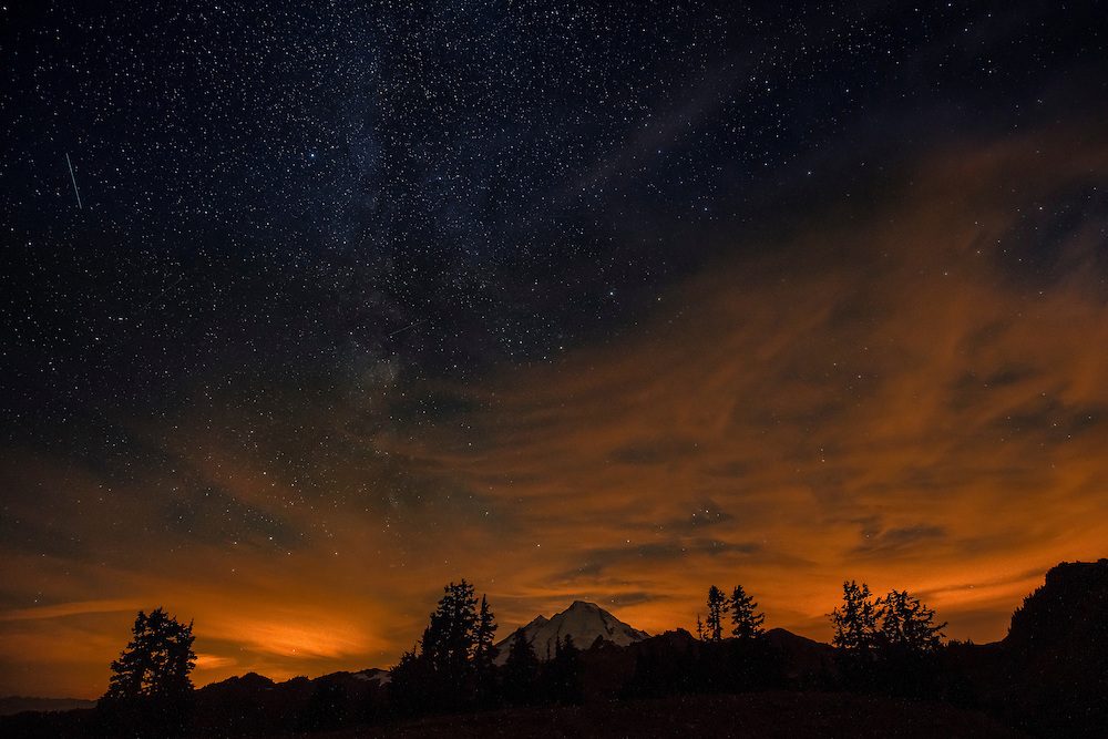 Sunset colored clouds linger in a star-filled sky over Mt. Baker, in the Cascade Range of Washington.