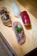Aji (horse mackerel) nigiri sushi in front of the wooden plate at the restaurant Yoshino Sushi Honten in Tokyo, Japan