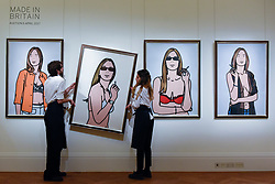 """© Licensed to London News Pictures. 31/03/2017. London, UK. Technicians hang """"Ruth Smoking"""", 2006, by Julian Opie (Est. GBP 30-50k).  Press preview of """"Made in Britain"""" at Sotheby's in New Bond Street.  The auction on 5 April celebrates innovative British art in the twentieth century as well as artwork by political cartoonist Gerald Scarfe. Photo credit : Stephen Chung/LNP"""