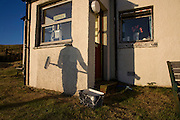 Warm evening sunshine casts shadow of decorator and his roller on hilltop cottage wall in hamlet of Hallin, Waternish, Skye