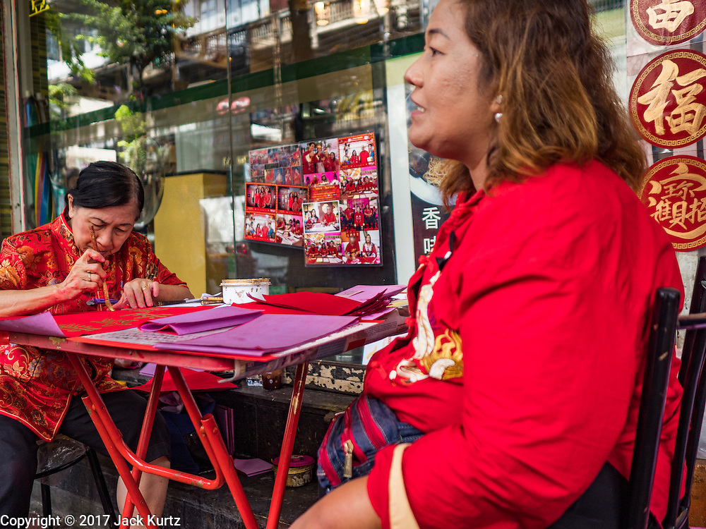 """18 JANUARY 2017 - BANGKOK, THAILAND: A traditional Chinese calligrapher draws New Years greetings that she sells in Bangkok's Chinatown district, before the celebration of the Lunar New Year. Chinese New Year, also called Lunar New Year or Tet (in Vietnamese communities) starts Saturday, 28 January. The coming year will be the """"Year of the Rooster."""" Thailand has the largest overseas Chinese population in the world; about 14 percent of Thais are of Chinese ancestry and some Chinese holidays, especially Chinese New Year, are widely celebrated in Thailand.<br />       PHOTO BY JACK KURTZ"""