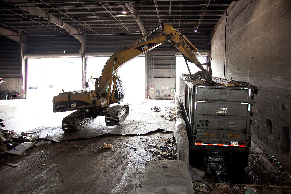 track-hoe loading solid waste into a transfer truck inside a waste transfer station
