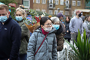 Columbia Road Flower Market busy with shoppers on 6th of December 2020 in Hackney, London, United Kingdom. The flower market in East London is on all year around for all kinds of plants and flowers but at Christmas time, many come to buy their Christmas tree and decorations for the festive season. The national lockdown 2 has just ended and London is under tier 2. The pandemic is still raging so many wear face masks, even outside, because of the lack of social distancing.