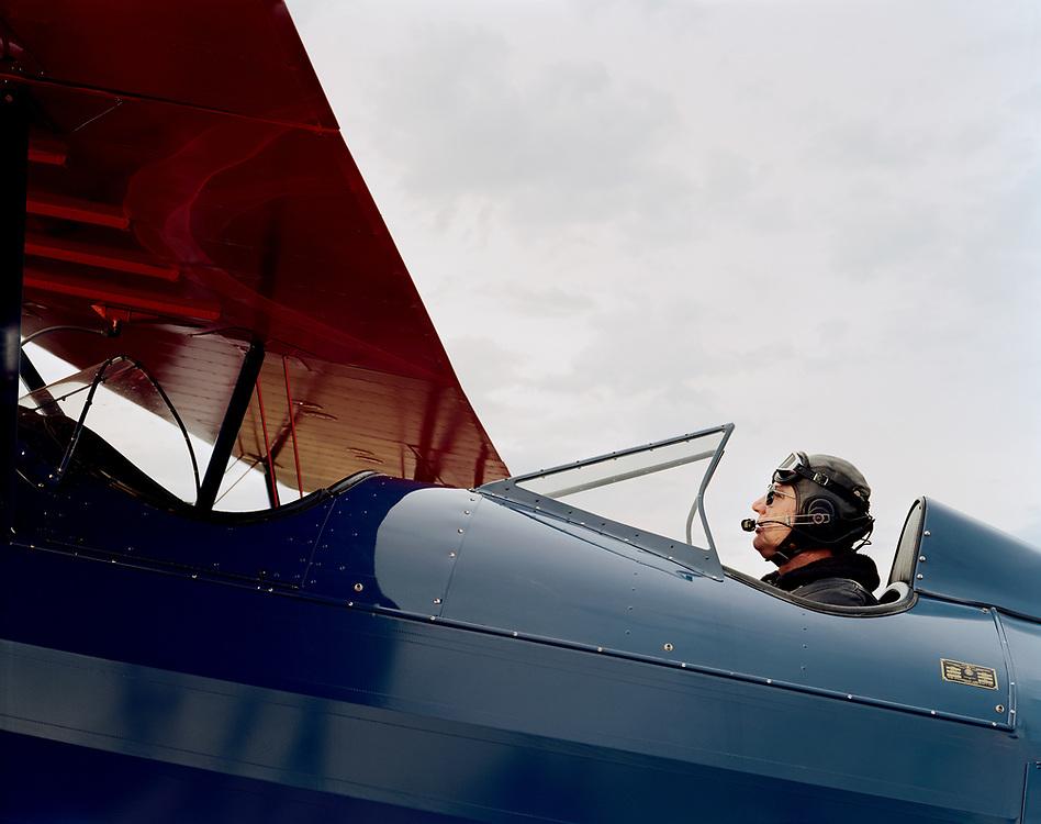 Older man sitting in cockpit of vintage biplane.