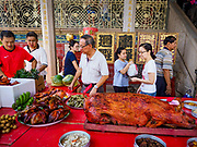 25 AUGUST 2018 - GEORGE TOWN, PENANG, MALAYSIA: People in Leong San Tong Khoo Kongsi Temple walk around the banquet for the spirits on Ghost Day, the full moon day (or night) that falls in the middle of Hungry Ghost month. The Ghost Festival, also known as the Hungry Ghost Festival is a traditional Taoist and Buddhist festival held in Chinese communities throughout Asia. Ghost Day, is on the 15th night of the seventh month (25 August in 2018). During Ghost Festival, the deceased are believed to visit the living. In many Chinese communities, there are Chinese operas and puppet shows and elaborate banquets are staged to appease the ghosts.     PHOTO BY JACK KURTZ